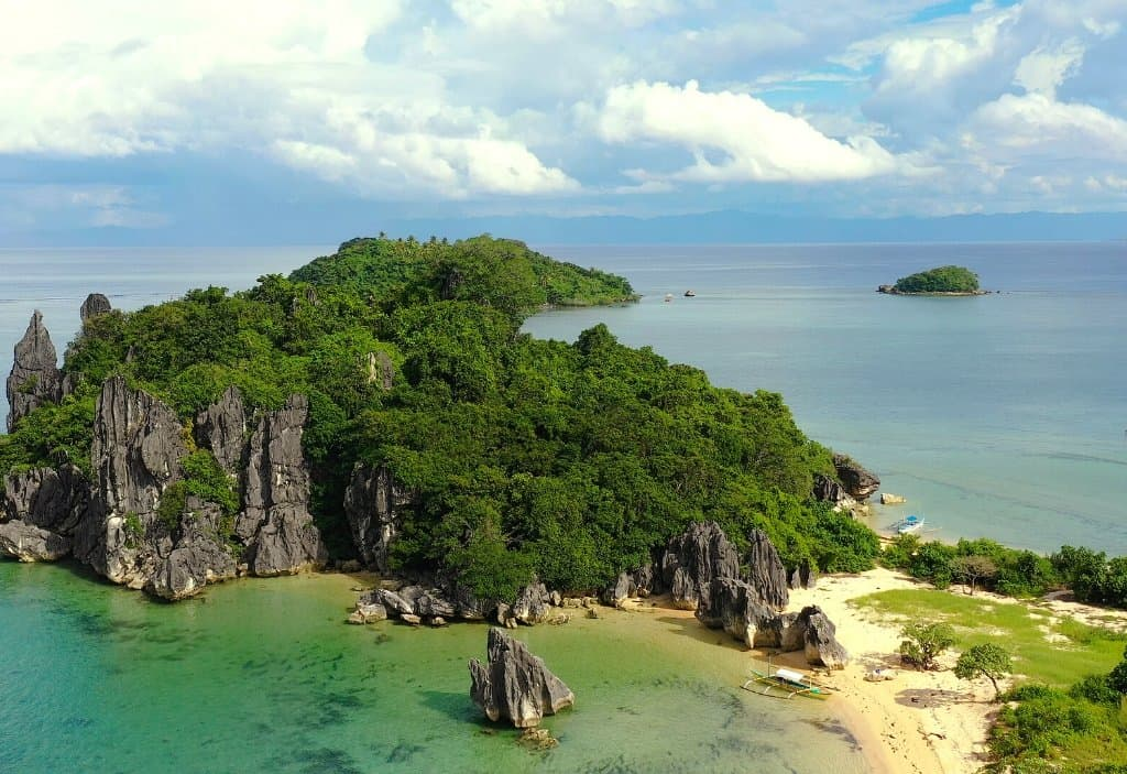 aerial view of the Caramoan Islands in Bicol Philippines with jagged limestone rocks and green jungle covering the rocks as well as golden sand beaches in Bicol