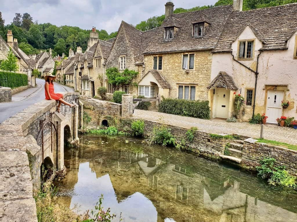 girl in red dress sits on old cotswolds stone bridge with the village of Castle Combe with yellow bricks in background, one of the most beautiful villages in The Cotswolds