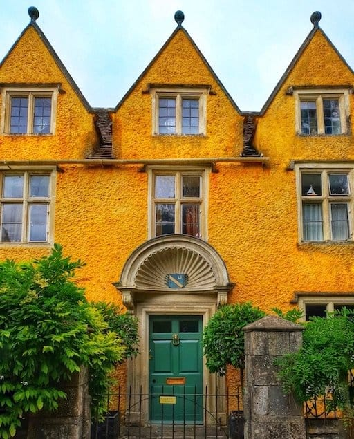 yellow house with green door and three spires on the top, very unique house in the cotswolds villages of castle combe in england