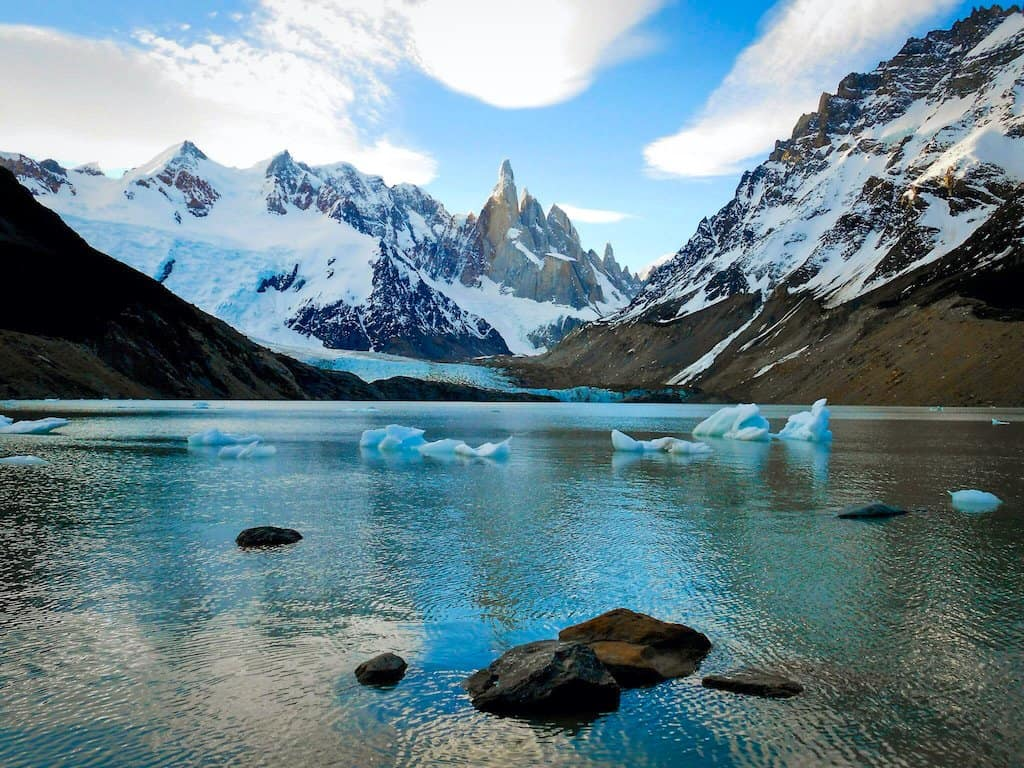 icebergs float in lake infront of jagged snow capped mountains in el chalten in patagonia argentina