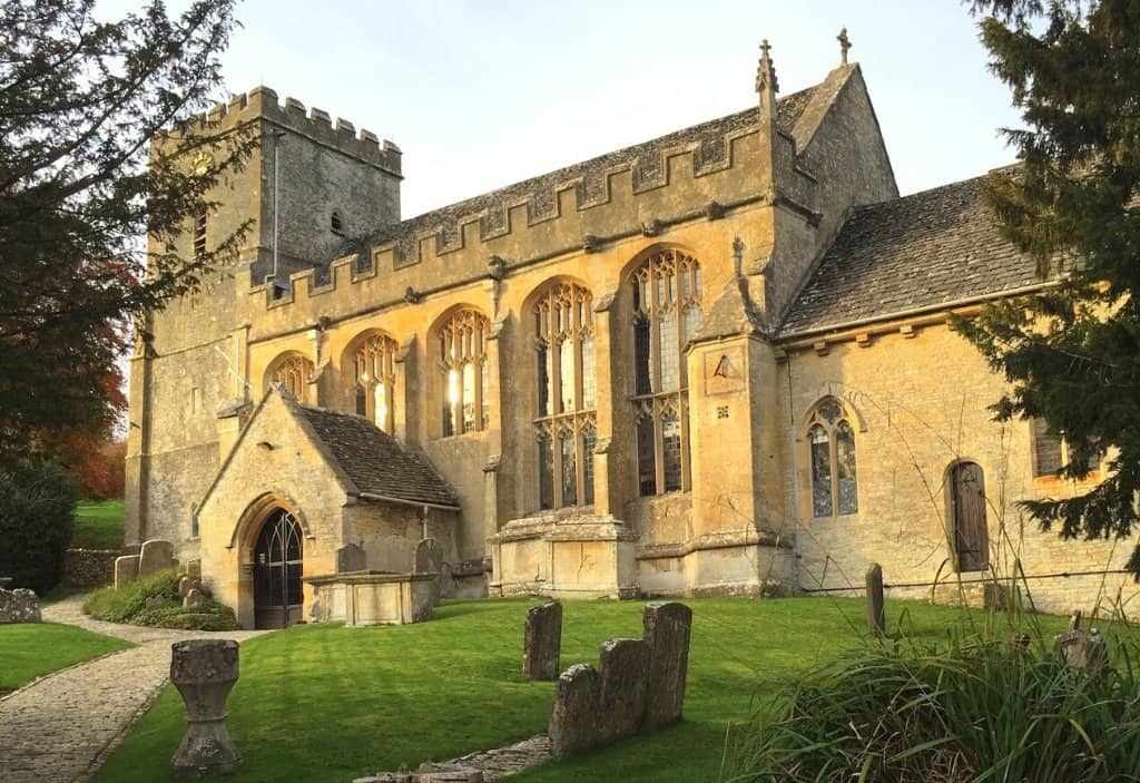 a big old church made from cotswolds stone in honey coloured with green grass and gravestones infront. This is a church in chedworth a cotswolds villages in england