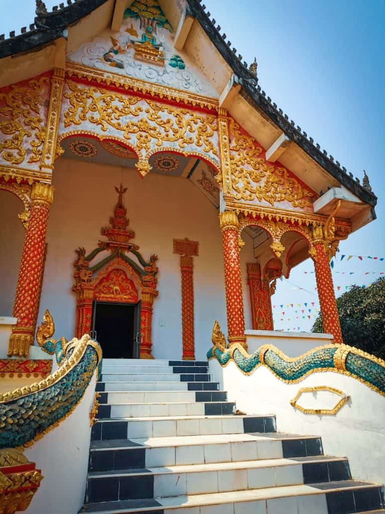 close up of a white Buddhist temple with red and gold decorations and a green dragon in Vang Vieng Laos