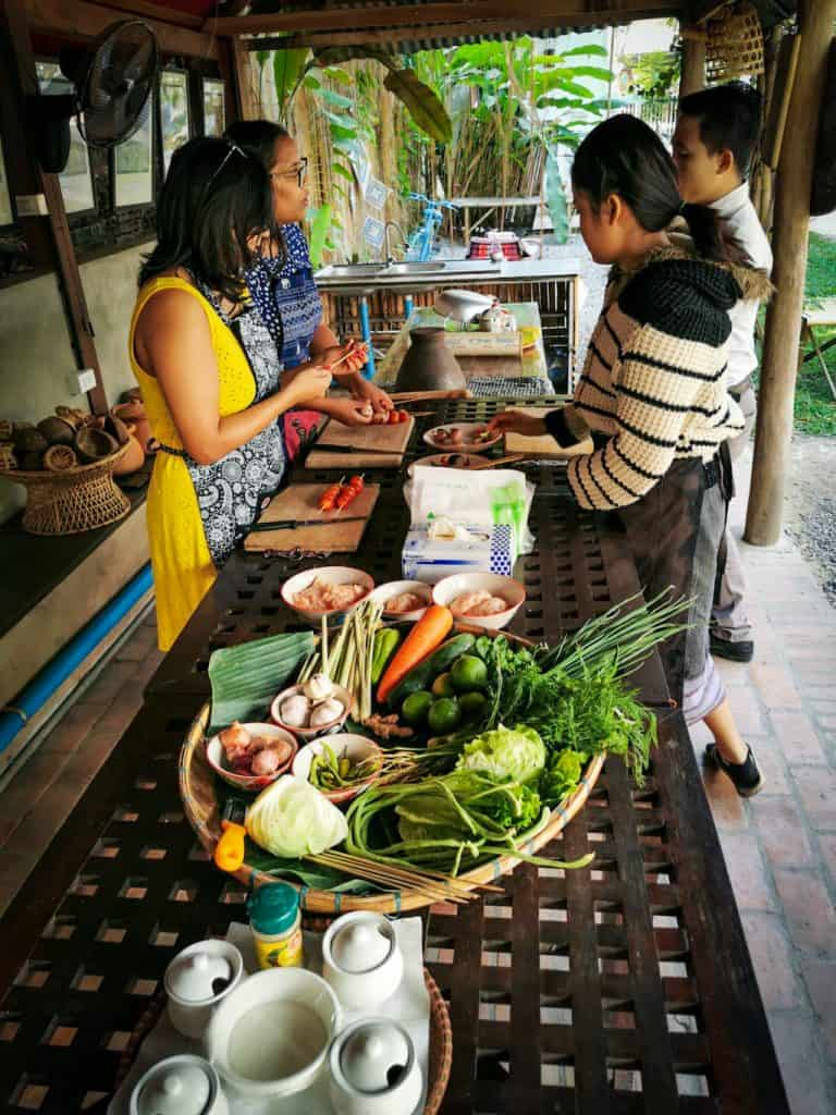 4 people are cooking in a cooking class in laos with fresh vegetables being chopped