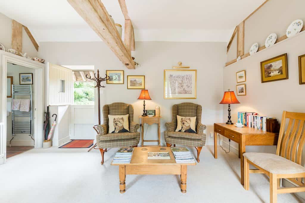 Cotswold cottage barn airbnb inside with chairs, beams and wooden furniture in cotswolds england