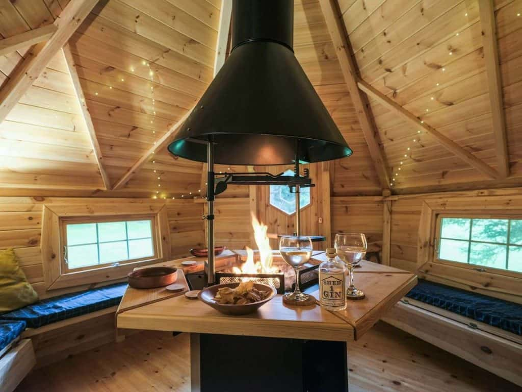 lake district accommodation airbnb inside of scandinavian yurt with wood burner in centre and seating around