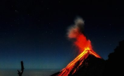 close up of an active volcano in guatemala called fuego exploding with orange lava and smoke filling the night sky