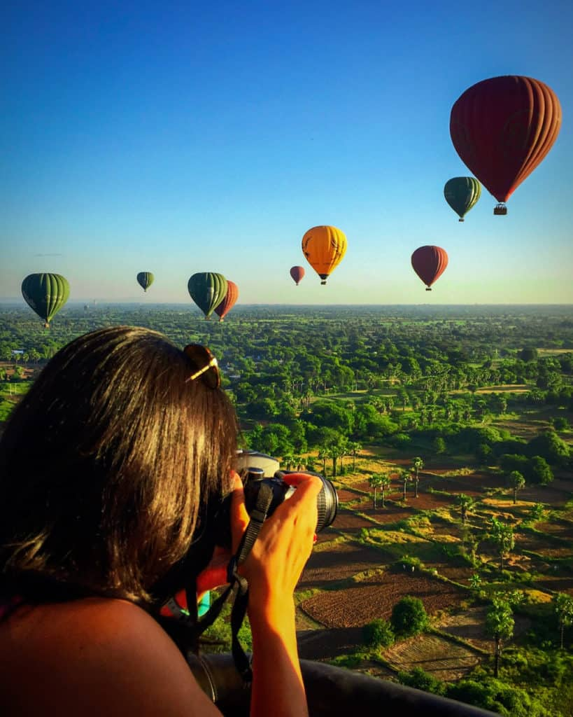 girl with camera is photographing hot air balloons in the sky over bagan in myanmar whilst she is in a bagan hot air balloon herself