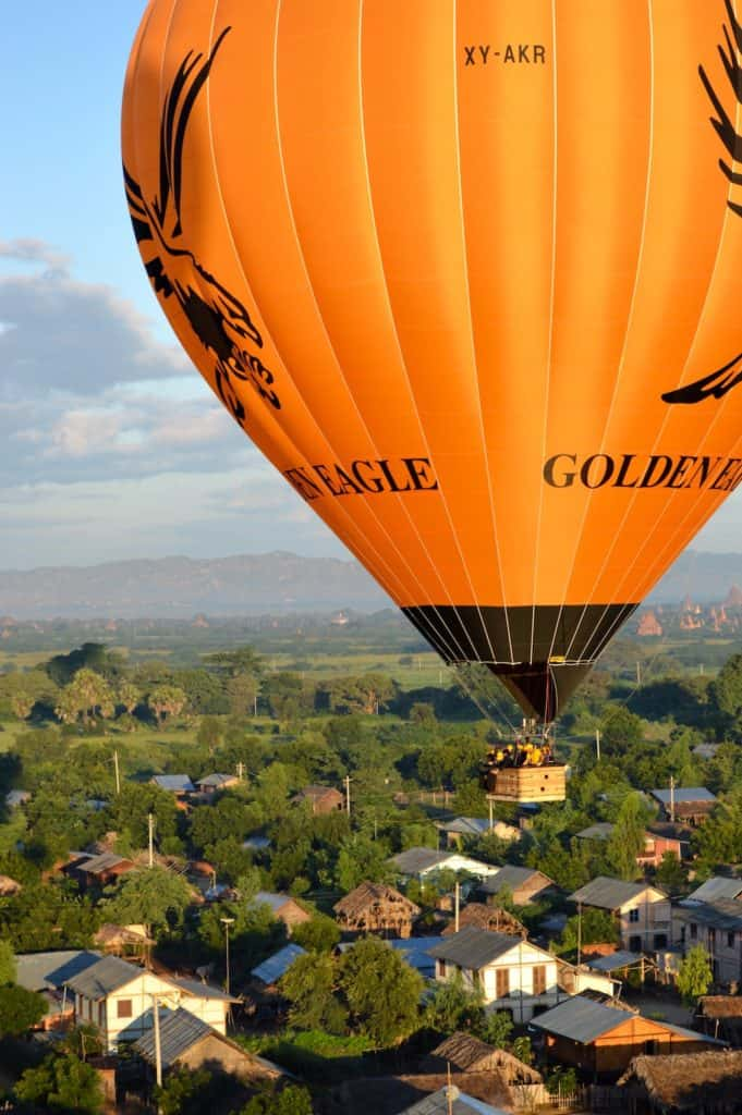 close up of yellow golden eagle ballooning bagan hot air balloon flying over a village and houses and trees in myanmar