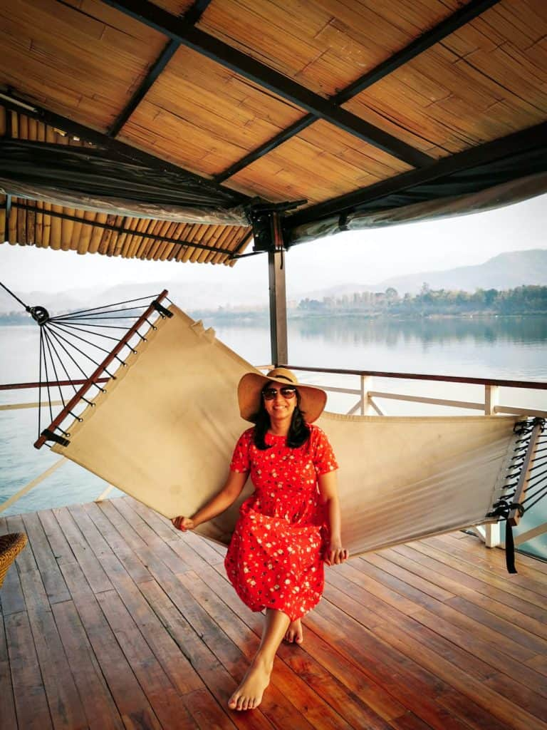 girl in red dress sits on hammock on a river boat in laos