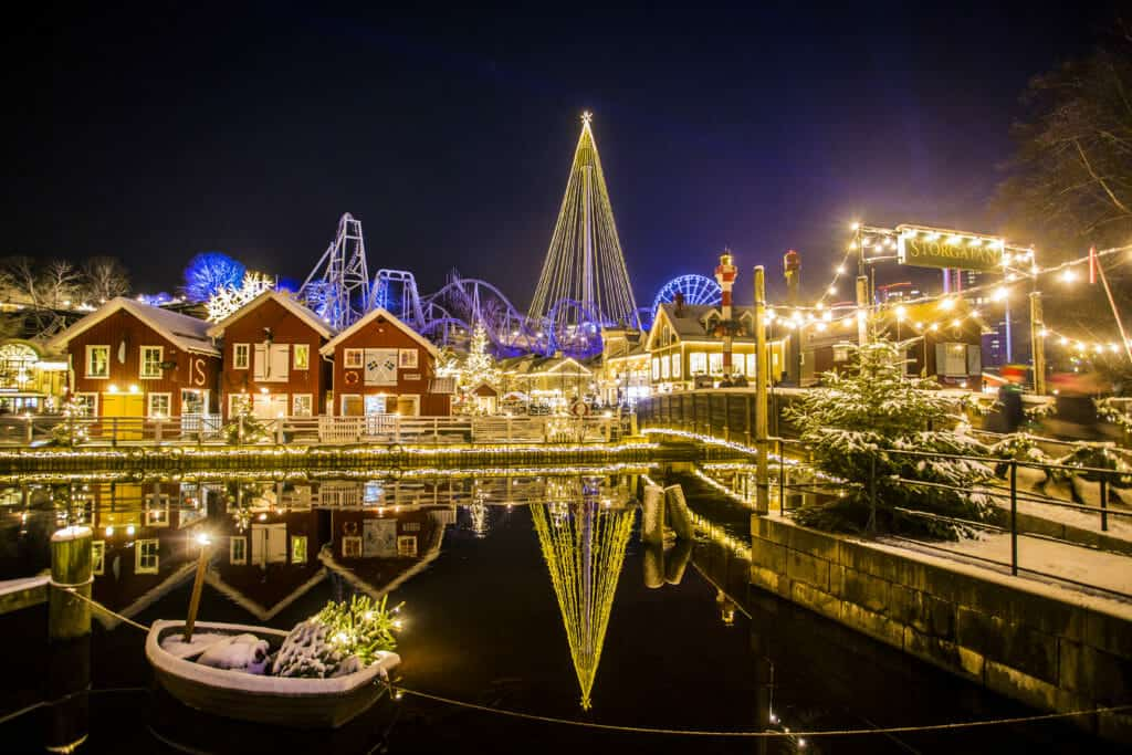 liseberg christmas market in sweden gothenburg all light up with neon christmas lights there is a canal and red buildings and a big christmas tree
