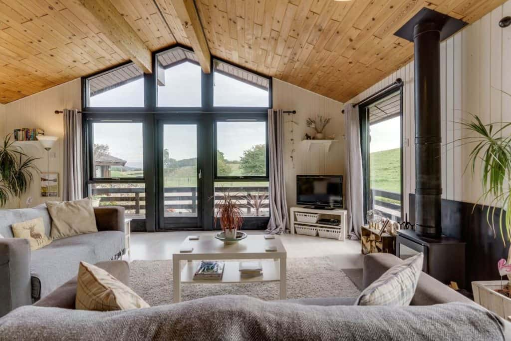 airbnb log cabin lake district with big living room, sofa, tv and view of outside with floor to ceiling glass windows