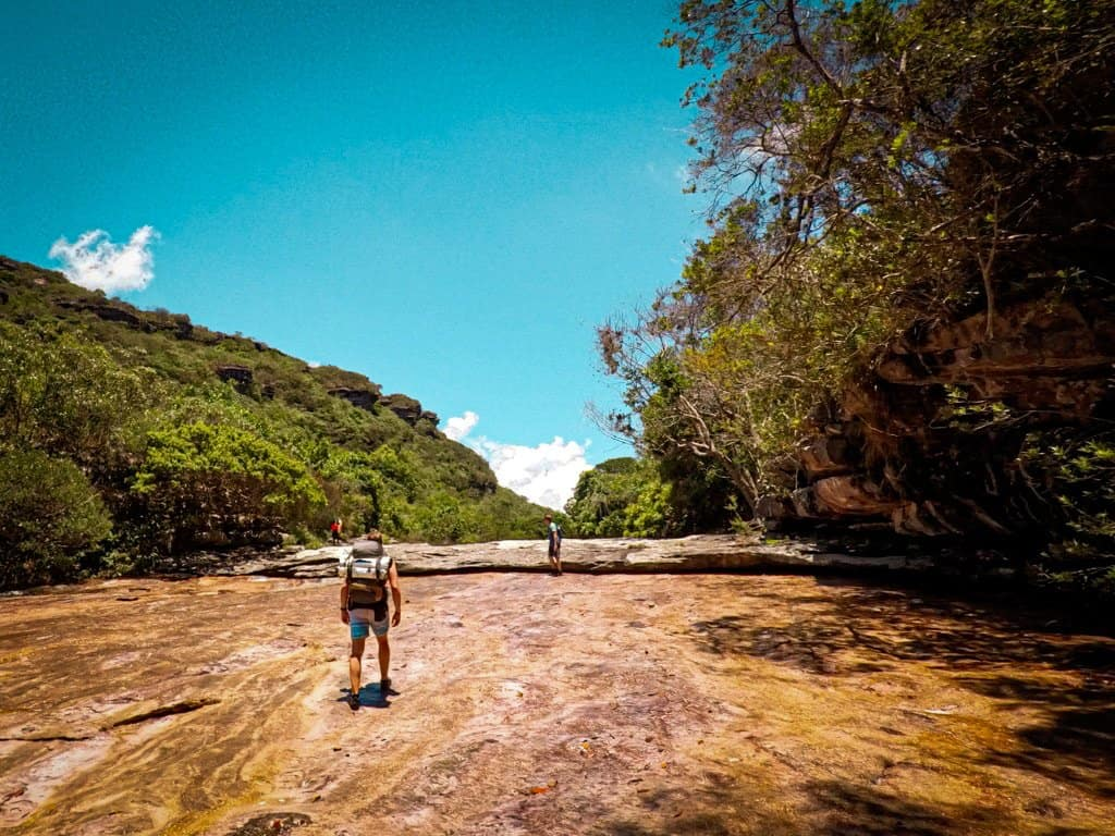 man with a backpack hikes through wilderness to mixilo waterfall in Chapada Diamantina brazil one of the best hikes in south america