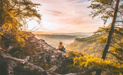 hiking quotes - girl sits on mountain looking out onto trees and landscape after a hike