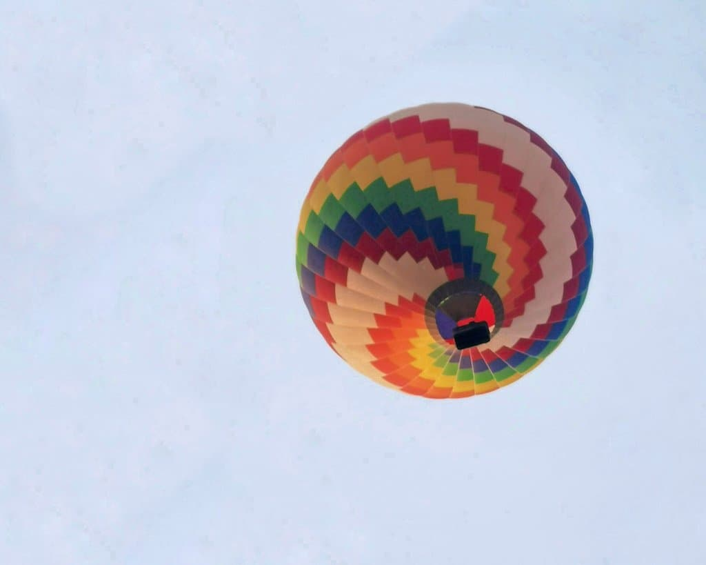 close up of a colourful striped hot air balloon in the sky from below it is one of the best things to do in Vang Vieng Laos