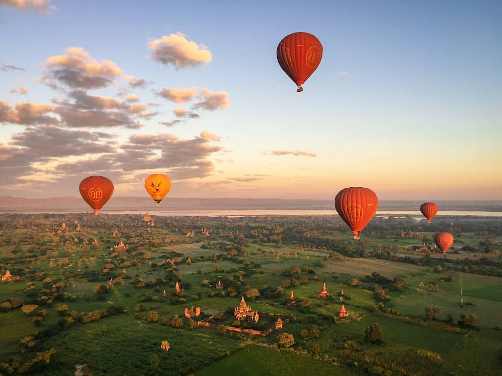 6 hot air balloons float over the temples and greenery of bagan in myanmar at sunrise
