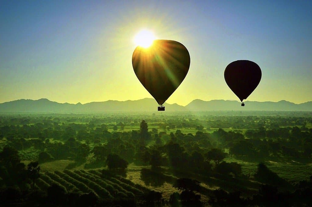 silhouettes of two Bagan hot air balloons at sunrise over a green lush countryside and with the sun just behind one of the balloons it is about to eclipse it in bagan
