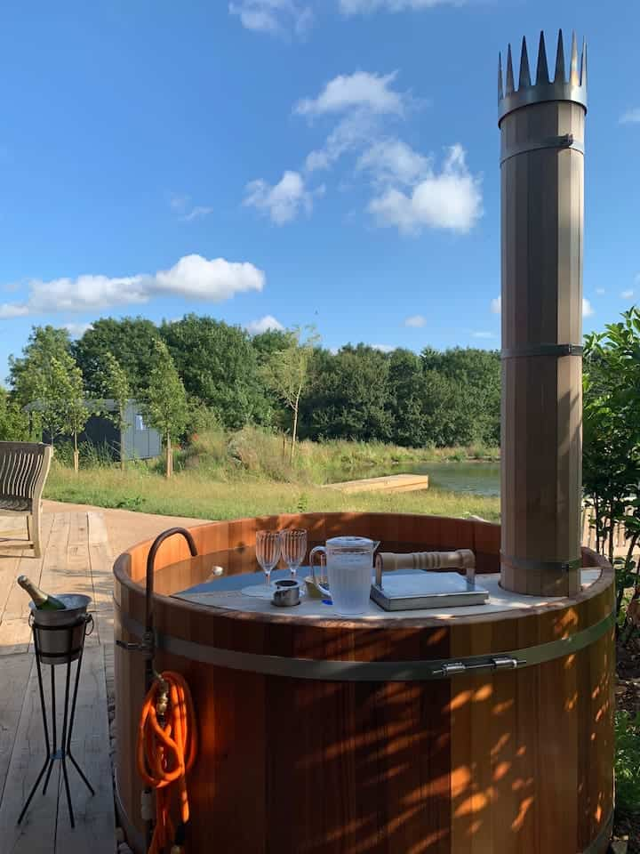 Self Contained Luxury Lodge with Hot Tub airbnb cotswolds. hot tub has wood burner with views of countryside