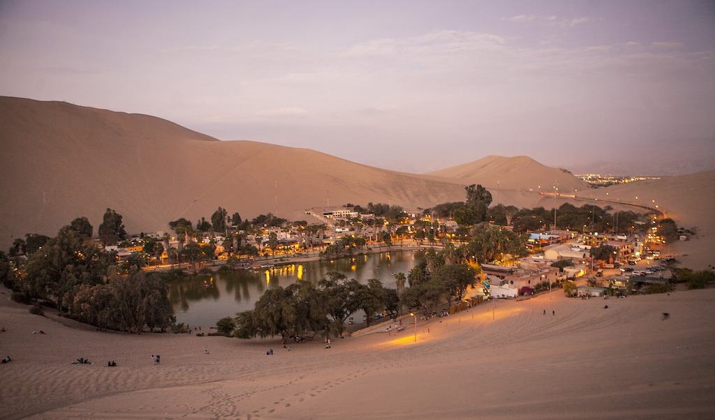sunset view of desert oasis with a town around the water pool in huacachina in Peru