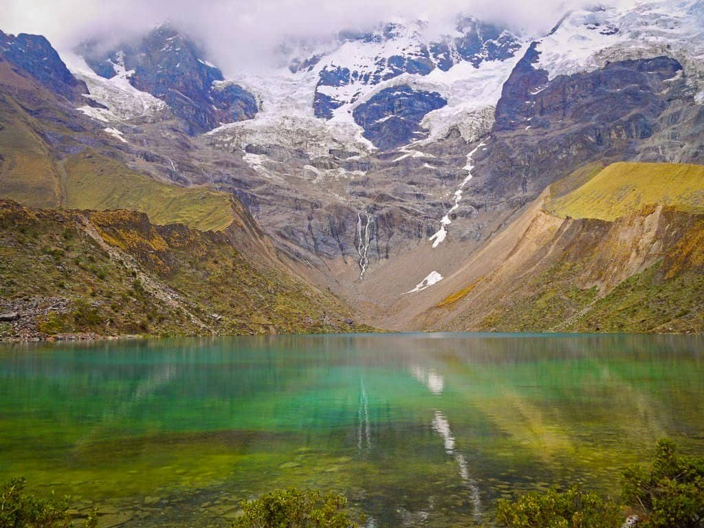 green lake with snow capped mountains in peru on salkantay hike