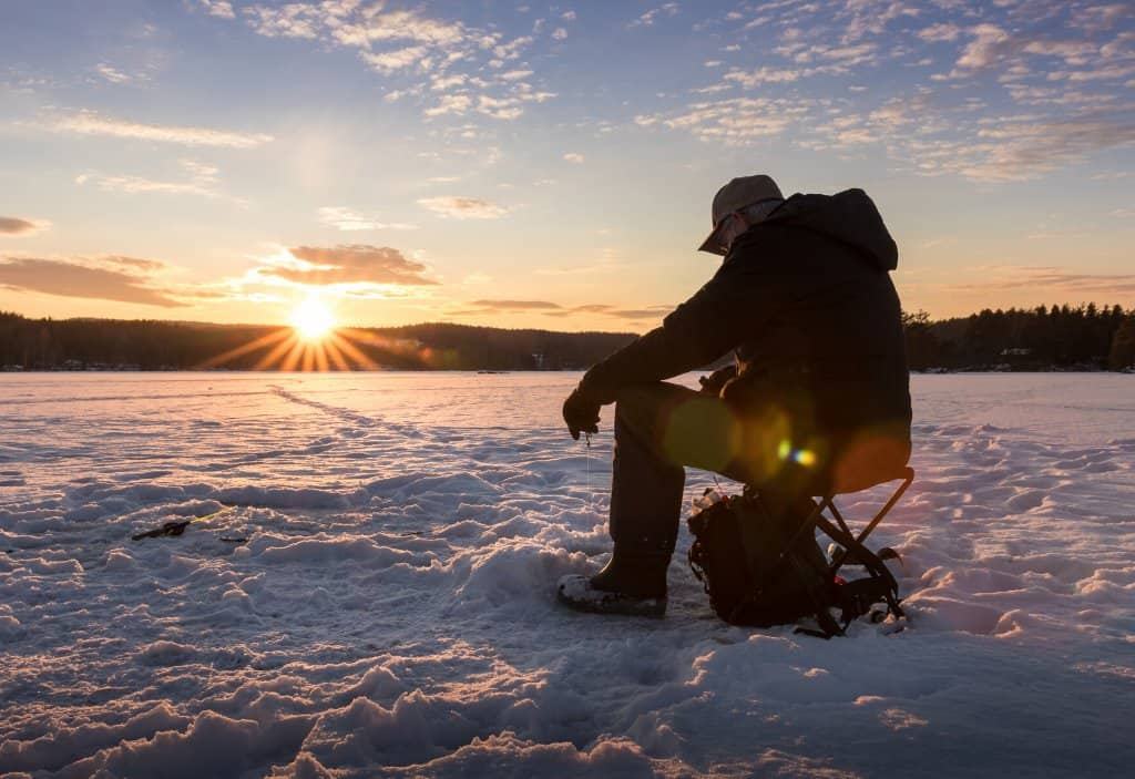 a man on ice fishing in the snow with sun setting in background in Alta Norway one of the best things to do in winter in norway