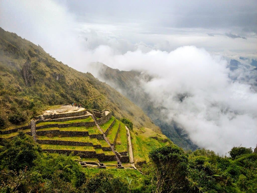 green mayan structures are in the clouds in peru on inca trail best hikes in south america