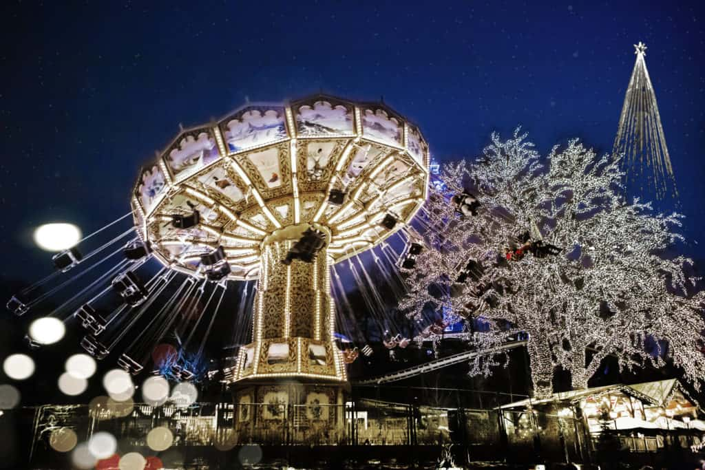 spinning rides and christmas trees decorated in lights at night time
