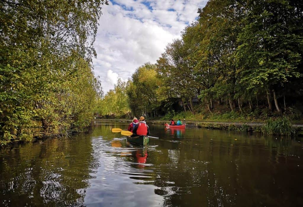group canoe along a canal with greenery on either side in sheffield on a microgap adventure