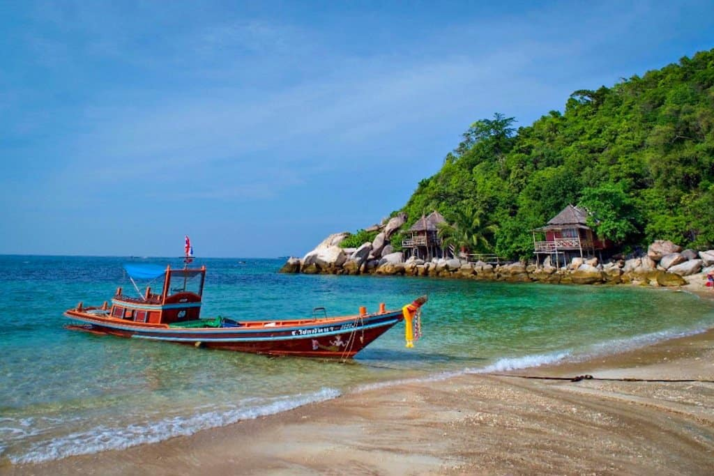 a long tail boat on a beach with palm trees in the background in Koh tao, Thailand - one of the beautiful islands in Asia