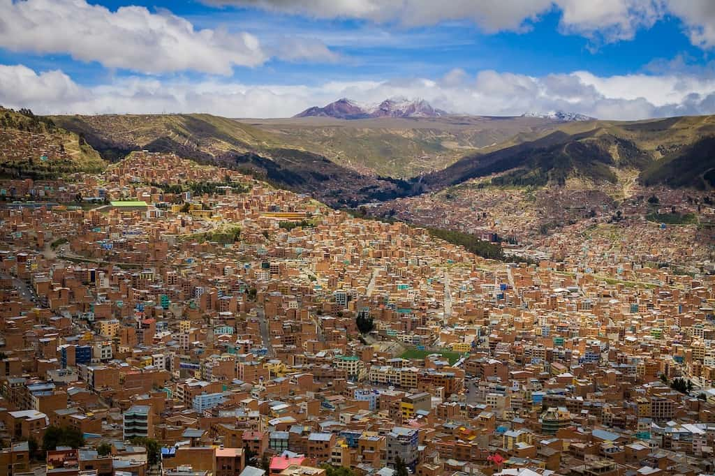view from high up of a built up city with thousands of houses and mountain views in the background