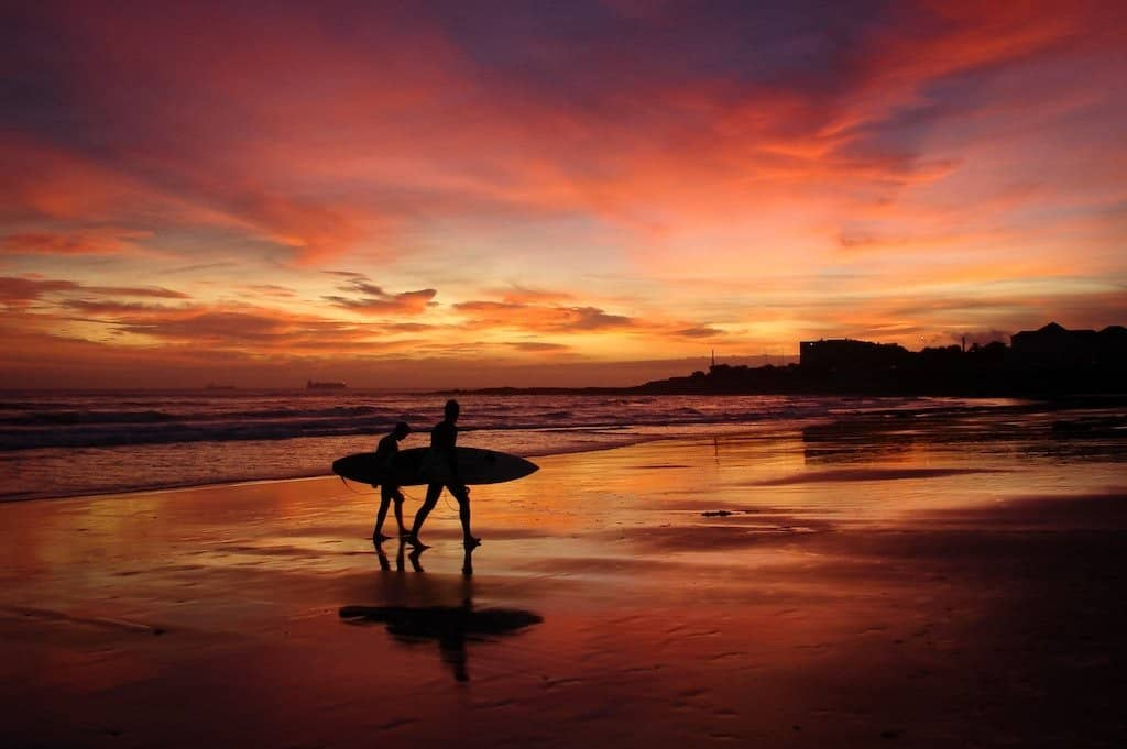 two people with surf boards walk across a beach with a red and orange sunset in the background in las penitas nicaragua