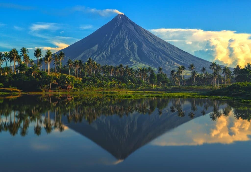reflection in water of a perfect conical volcano with palm trees and clouds behind it in Legazpi City, the volcano is Mount Mayon and is famous in Bicol Philippines