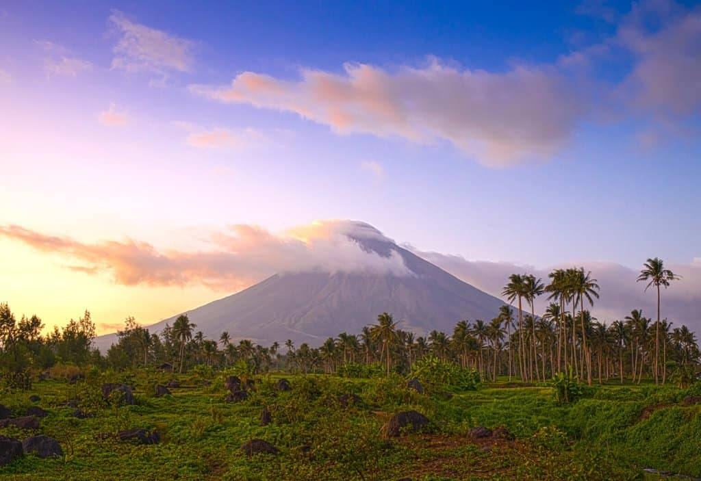 perfect conical shaped volcano with greenery and palm trees in front and purple sunset sky