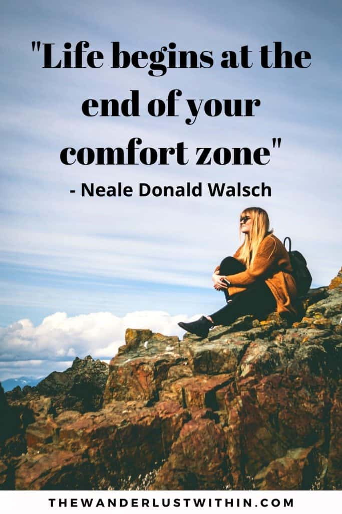 motivational inspirational solo travel quote saying life begins at the end of your comfort zone by neale donald walsch with a girl sitting on a rock looking over at views of mountain alone