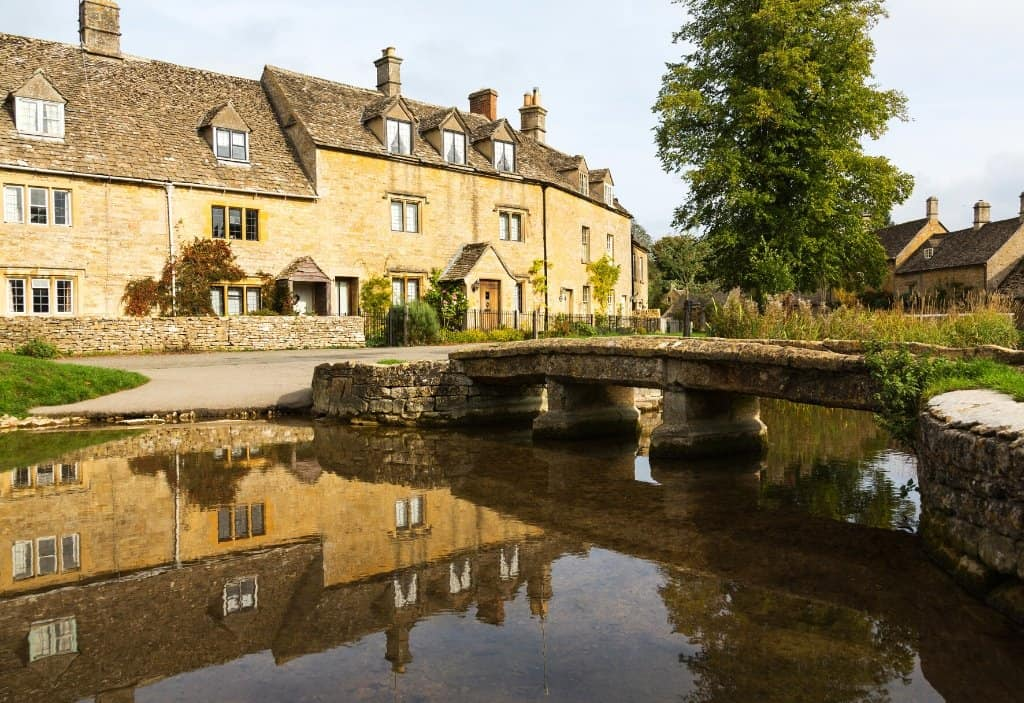 a row of cotswolds houses with a river stream in front of it and a stone bridge in the cotswolds village of lower slaughter
