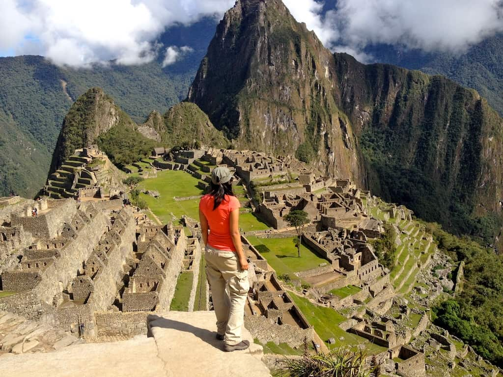 girl in orange top and beige khaki trousers looks over view of Machu Picchu in Peru