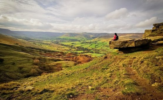 girl in pink sits on edge of rock with views of english countryside in front of her, there are autumnal colours of green yellow and orange landscapes in peak district
