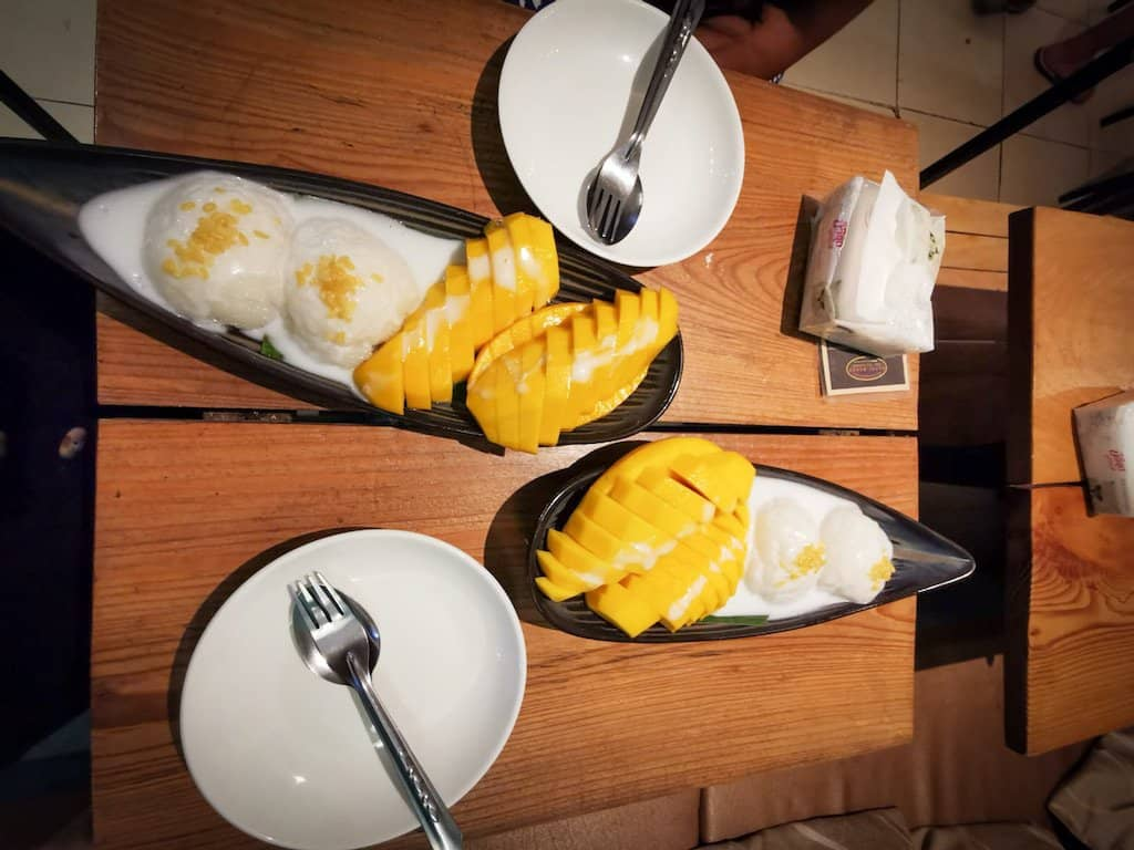 two portions of mangos and white sticky rice on a plate waiting to be eaten at happy mango restaurant in Vang Vieng one of the best things to do in Vang Vieng Laos
