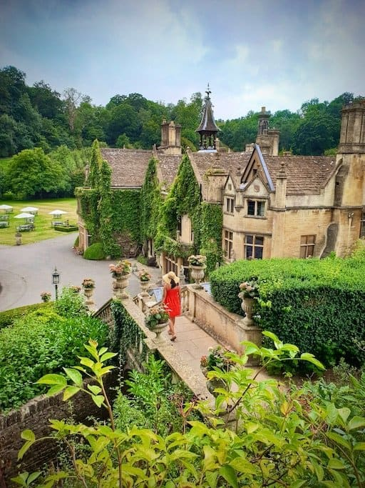 girl in red dress walks along a path surrounded by greenery in front of a big mansion estate in castle combe in the cotswolds england with greenery climbing up the walls of the old building in villages in england