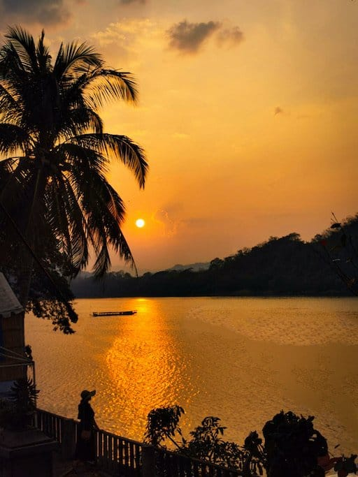girl looks out over Mekong River with an orange sunset, palm trees and boat silhouette in Luang Prabang laos