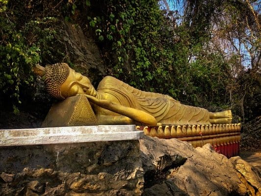 sleeping gold buddha statue in laos in Luang Prabang on top of mount phousi