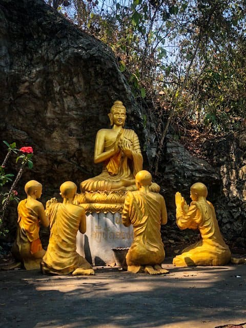 4 gold buddha statues stand next to a rock on the top of mount phousi in Luang Prabang