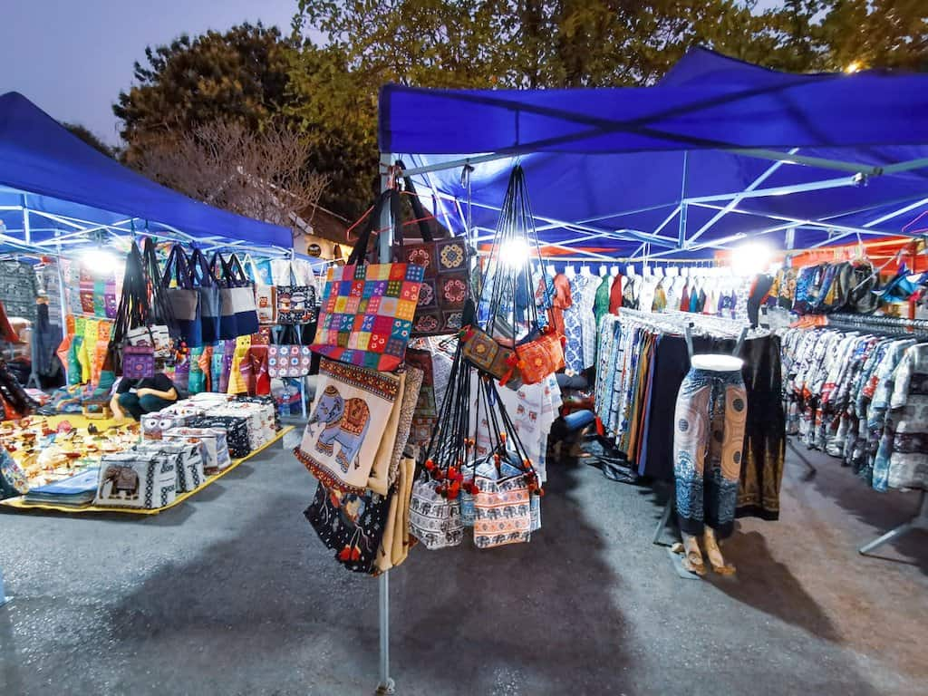 stalls of products made in laos are in a night market under a blue canopy in luang prabang