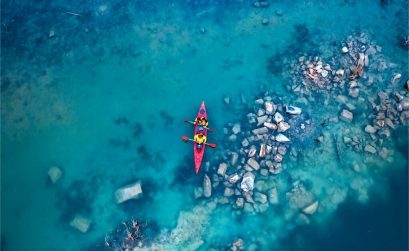 two men kayaking in red kayak through blue water and rocks perfect for outdoor quotes
