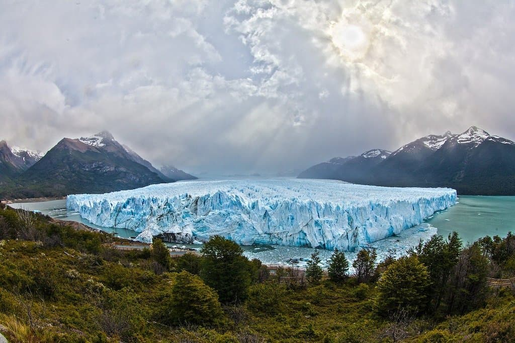 aerial view of ice glacier and snow capped mountains in the distance in Argentina best hikes in South America