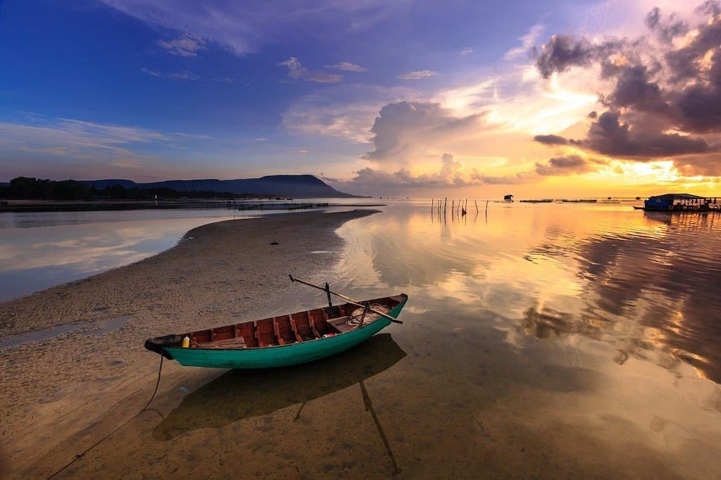 a green boat on a sandy beach with a sunset in the background in php Quoc an island off Vietnam and is the most beautiful island in asia