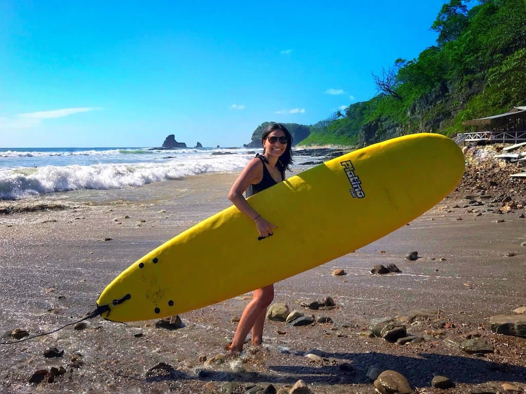 girl holds yellow surf board on a beach in nicaragua