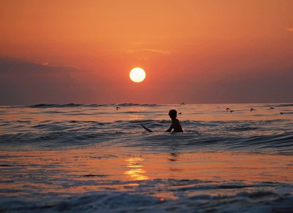 man on popoyo beach at sunset on surf board with red sun and sky in background in best towns nicaragua