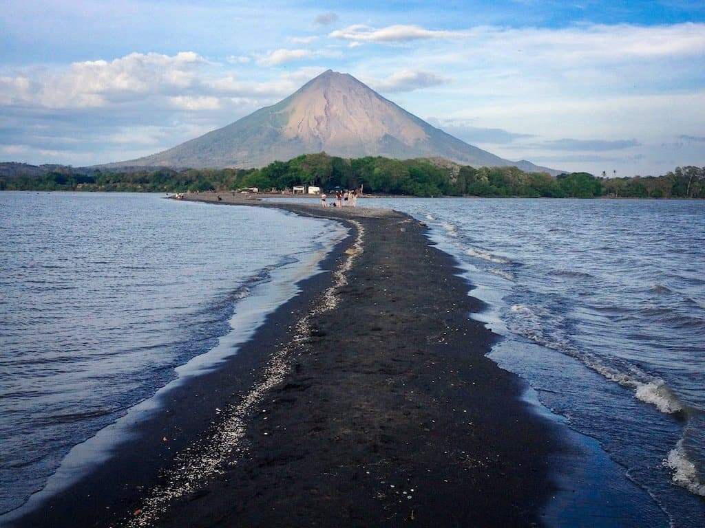 volcano with lake under it and a black sand beach splitting the lake in Isla Ometepe Nicaragua