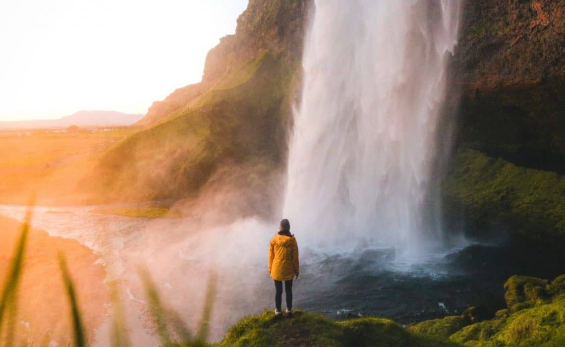 person in yellow stands with waterfall in front waterfall quote