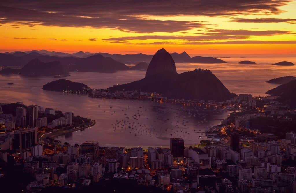 quotes about sunrise - sunrise on sugarloaf in rio de janeiro with pink and orange sky and coastline, buildings and odd shaped mountain in center